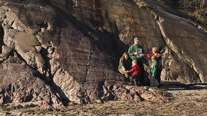 Des guides du Géoparc de Stonehammer, au Nouveau-Brunswick, expliquent l'histoire du site géologique aux visiteurs.